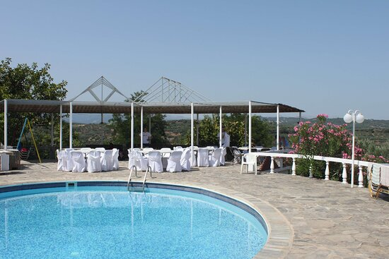 Crète, Grèce : Relax by the pool with a breathtaking backdrop of olive trees and the sea.