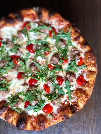 The Pretentious GOAT: our original calabrese-honey-sausage, finished with peppadew peppers, arugula, and goat cheese.