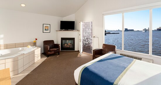 One Room Waterfront Suites feature a whirlpool, fireplace, private balcony and queen bed. Most of these units are on the second floor and have a spacious, vaulted ceiling. Pictured here is a Harbor View One Room Waterfront Suite.