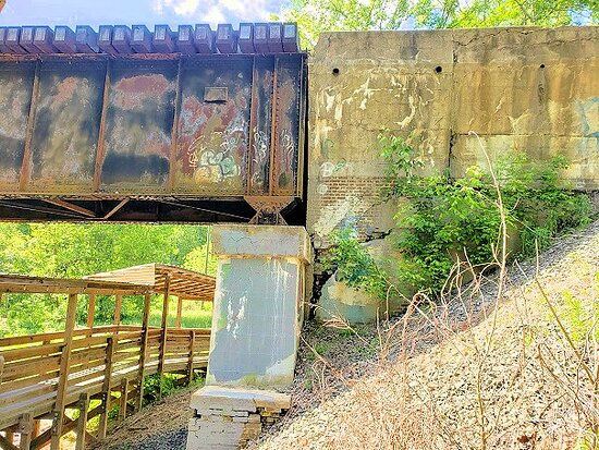raised walk along river under railroad bridge