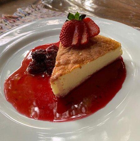 Cheesecake de chocolate branco com um toque azedinho de creme de queijo. Servido com calda de frutas vermelhas.