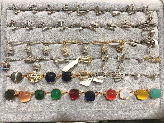 Anelli in bigiotteria con iniziale, campanelli e pietre
