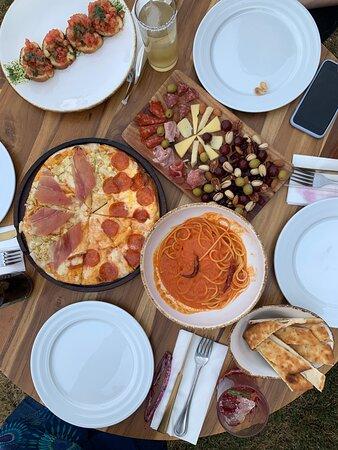 Nuestra comida: bruschetas, tabla de quesos, carnes frías, aceitunas y nueces, pizza y pasta. Todo delicioso.