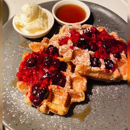 Waffles with berries, maple syrup and ice cream