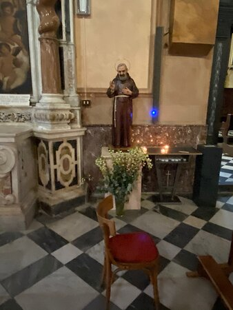 Second altar to the left: the Holy Trinity. The work, executed at the end of the sixteenth century, is difficult to attribute. In the center of the altar frontal stands the coat of arms of the Scofferi family: three lilies of France and a heart.Next to it is a little satue of St. Padre Pio.