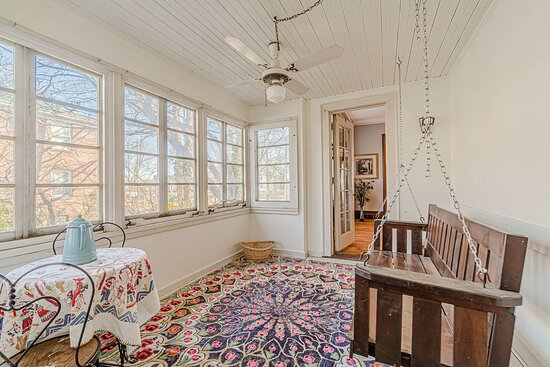 The enclosed side porch even has a swing!