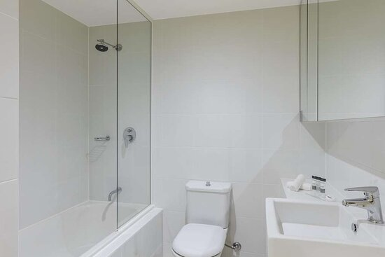 Interior view of bathroom in One Bedroom Suite with shower in bathtub and vanity