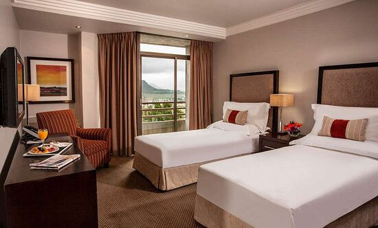 Interior view of bedroom in Avani Twin Room with twin beds, desk and mountain view