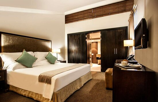 Interior view of bedroom in Avani Superior Room with king bed and bathroom view