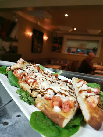 Start your dinner with Tomato Bruschetta on a flatbread