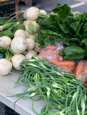 A selection of early summer vegetables, including garlic scapes, at the Hudson MA Farmers' Market.