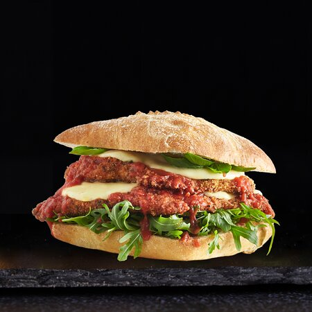 Parmi Artisan Sandwich  Known as 'food valley', the northern Italian city of Parma is a food lovers delight and home to some of Italy's famous food products including Parmigiano-Reggiano, Prosciutto di Parma and, of course, the Parmigiana.  Herb-Crumbed Chicken Schnitzel + Melted Mozzarella Cheese + Fresh Basil Leaves + Rocket + Napolitana Sauce on our Freshly Baked Pain de Campagne Diamond Bun