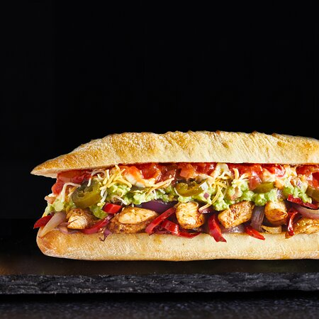 El Mexicano Artisan Sandwich  Authentic Mexican food is vibrant, delicious, fresh and fun. We've put a twist on the traditional flavours and turned it up a notch with this colourful and spicy creation.  Grilled Chicken Marinated in Fajita Seasoning + Sautéed Red Capsicums and Onions + Shredded Three Cheese + Guacamole+ Jalapeno + Sour Cream + Pico De Gallo on our Freshly Baked Pain de Campagne Roll
