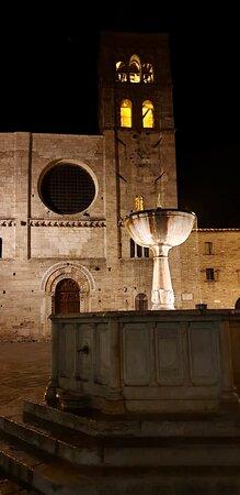 Una calda illuminazione impreziosisce la facciata della splendida chiesa di San Michele Arcangelo (Xll sec) e la fontana risalente alla fine dell'Ottocento. Marzo 2019