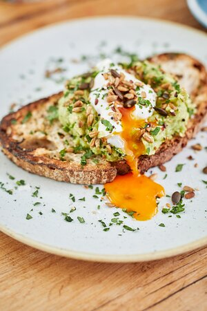 Avocado & poached egg on sourdough toast at brunch.