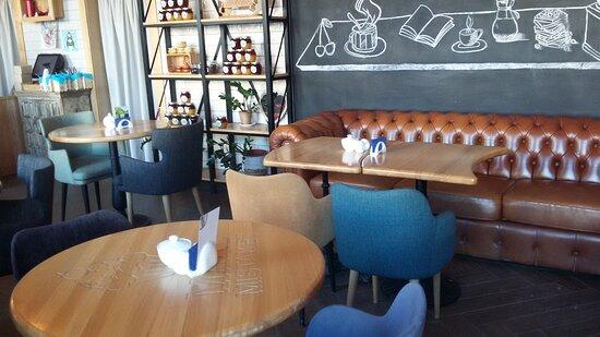 В основном зале кафе есть столы разной формы, а также стульчики, кресла и даже диваны!