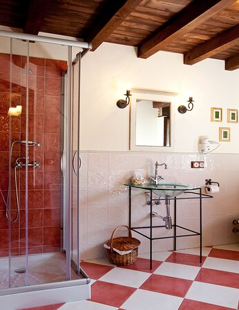 Baño de habitación superior (Birdie) con ducha y bañera de hidromasaje en esquina.