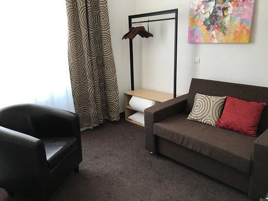 """petit salon pouvant se transformé en chambre avec canapé """"rapido"""" avec vrai matelas en 90 - en face du canapé se trouve une télévision écran plat avec casque"""