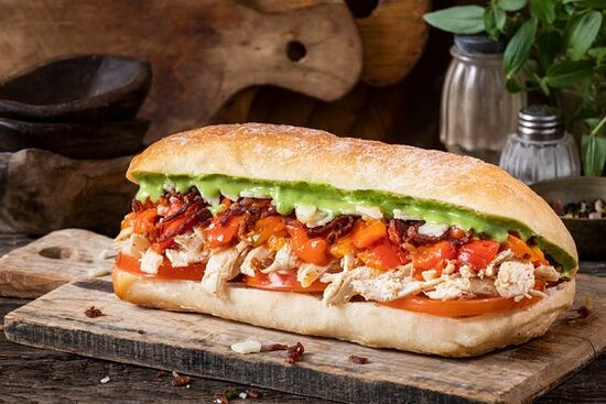 Pesto Bacon Chick Sandwich- Sandwich with shredded chicken, parmesan cheese, sliced tomatoes, beef bacon bits, roasted red peppers, and pesto sauce. Served on toasted ciabatta bread.