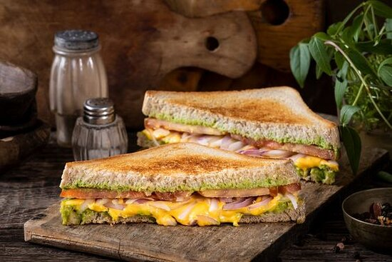 Papi Pesto Grilled Cheese- Grilled cheese sandwich with cheddar cheese, sliced tomatoes, red onions, and pesto sauce. Served on toasted brioche.