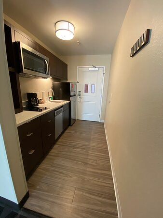 Kitchen with small dishwasher, refrigerator, microwave, coffee machine