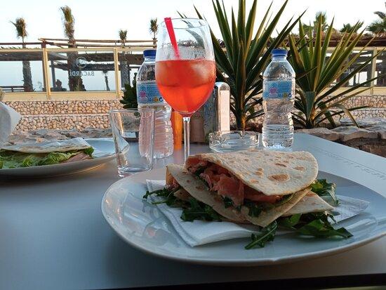 Jantar de família. Comer  Piadina maravilhosa  e bebida fresca italiana Spritz com vista linda para mar..