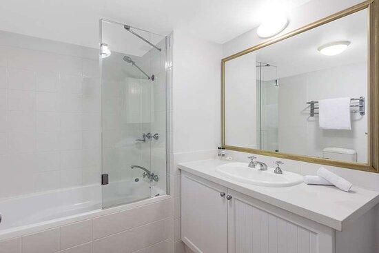 Interior view of bathroom in One Bedroom Ocean Premier Suite with bathtub and vanity