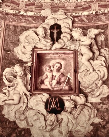 The altar is flanked on the apse wall by two pictures in elaborate, billowing putti-inhabited white stucco frames. The one on the right depicts St Philip Neri by Guido Reni, and the left is an icon of the Madonna and Child by Giovanni Battista Salvi, Il Sassoferrato.Outside the railings there are two polychrome marble Baroque memorials by Tommaso Righi showing the deceased at prayer and venerating the altar. One is to Nicola Maria Lercari 1767, and the other to Nicola Lercari 1784.