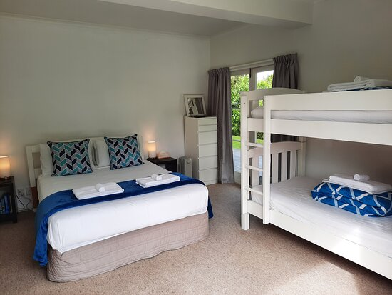 Room One has a queen bed and two bunk beds sleeping a total of six persons. The room opens to the north garden.