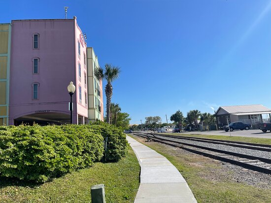 Side view of hotel with train tracks behind it and waterfront behind tracks.back of hotel.