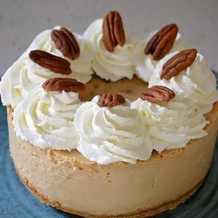 Salted Caramel Pecan Cheesecake: A lightly salted dulce de leche caramel cheesecake with a graham cookie crust, topped with whipped cream and toasted pecans.
