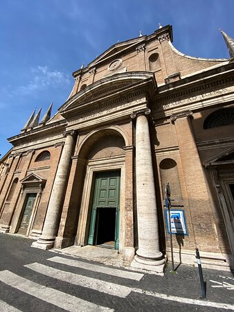 Façade. The building material is red brick, with architectural details in travertine. The composition is dominated by the entrance propylaeum, which has a pair of large stone Ionic columns in the round, supporting an entablature and a segmental pediment which intrudes into the upper storey.