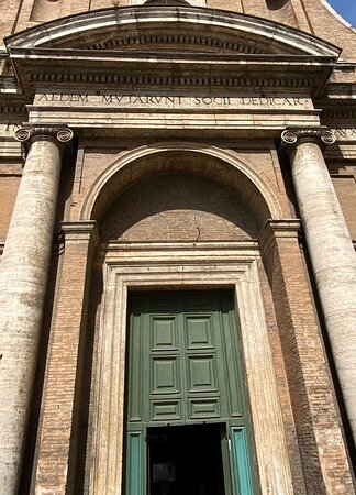 The propylaeum is brought forward from the plane of the façade, and within it is a recessed arch containing the actual doorway. The latter has plain moulding, and the former a pair of brick Doric pilasters fitting against the columns.The tympanum of the arch is empty and the stone capitals of the pilasters are extended across the façade as a string course.