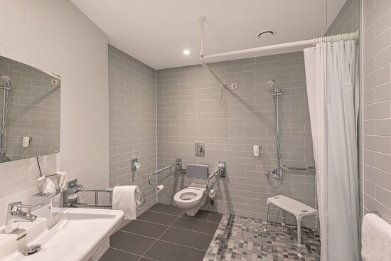 A spacious and attractively tiled accessible bathroom.