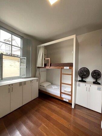 Quarto compartilhado com ventilador e banheiro externo.
