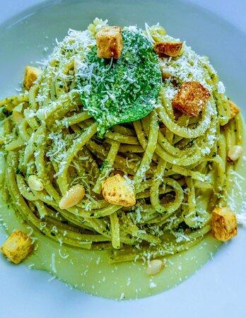 Spaghetti al pesto, papas en doble cocción, piñones tostados y parmesano