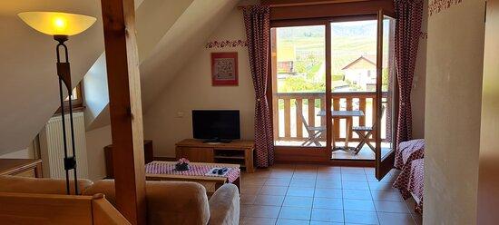 """mezzanine avec un salon donnant sur un balcon et coin chambre avec deux lits jumeaux de l'appartement """"Sébastien"""""""