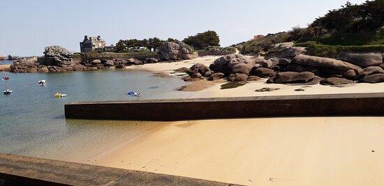 Vue sur la plage Pitet et la cale d'embarquement depuis les rochers de la plage du Coz Pors.  Côté Est de la plage du Coz Pors avec le sentier des douaniers vers l'île Renote à Trégastel Coeur de la Côte de Granit Rose.