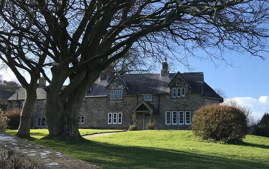 Wroxall, UK: Appuldurcombe Farm - The Farmhouse with large Willow and stone wall in the foreground. The Farmhouse sleeps 10 in five bedrooms. Willow Cottage can be seen behind the tree to the left. The two properties can be opened up to sleep 12 in six bedrooms.
