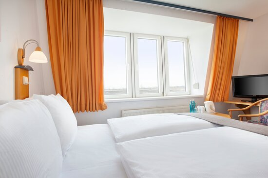 A well-lit room, with comfortable bedding and a satellite TV.