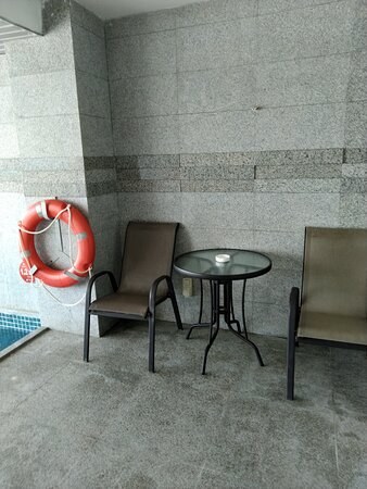Sitting area on the balcony with swimming pool.