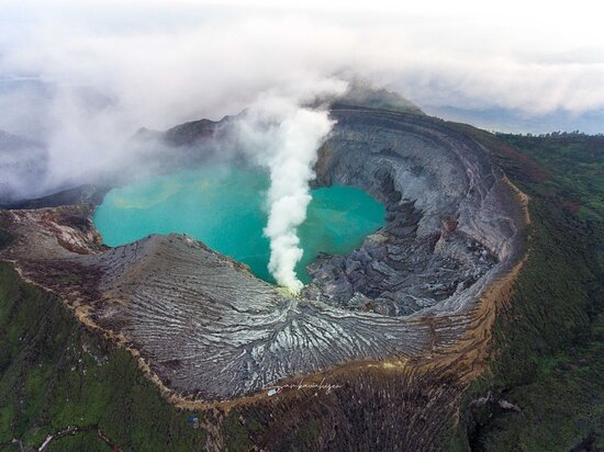 Indonesia's Kawah Ijen Volcano, on the island of Java, has two of the most unusual occurrences on Earth. The first is an active solfatara that emits hot, flammable sulfurous gases.  These ignite as they enter Earth's oxygen-rich atmosphere and burn with an electric blue flame. Some of the gas condenses in the atmosphere to produce flows of molten sulfurthat also burn with an electric blue flame. The flames are difficult to see during the day but illuminate the landscape at night.