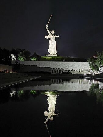 Ночью скульптура отражается в бассейне.