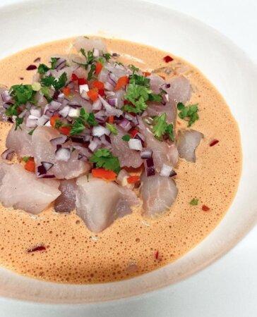 CRUDO DE PESCADO Cubos de pescado con cebolla y cilantro sobre salsa acevichada de erizos
