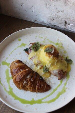 Яйцо пашот под обожженым соусом голландез на французском круассане с жареным беконом и шпинатом.