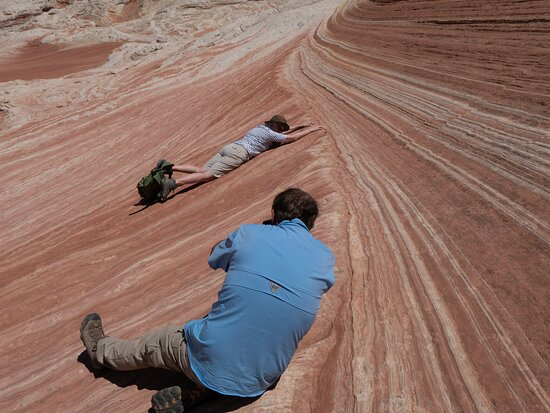 Hiking Kanab Visit and Photograph the famous White Pockets in Vermilion Cliffs: Bruce takes a funny picture - when image is rotated it looks like subject is hanging from a cliff..