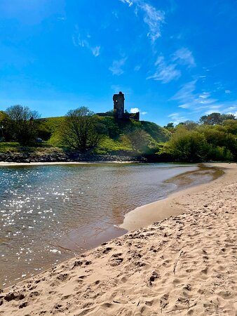 The sandy beach is split by the Lunan Water flowing into the sea, and overlooked by the romantically ruined 15th century Red Castle with it's precarious tower.