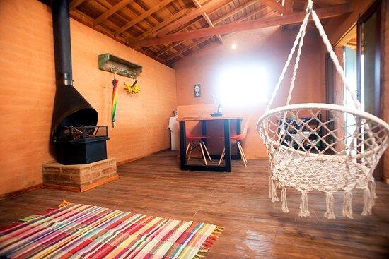 Corrego do Bom Jesus, MG: Espaço da lareira com cadeira de balanço em macramê e mesa perfeita para refeições e trabalho remoto.