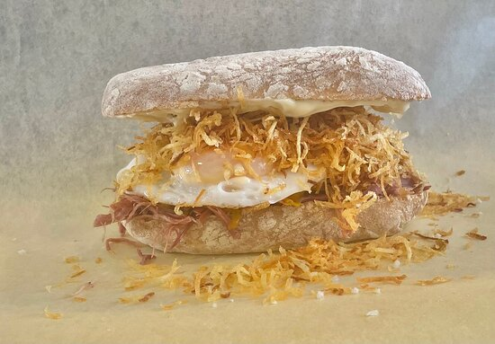 """Meet """"Max Halley"""" Ham, Egg and Chips!  inspired by the eccentric chef himself. This is our slow cooked ham hock with homemade piccalilli, a runny fried duck egg topped with shoestring fries and malt vinegar mayonnaise in a rustic ciabatta roll."""