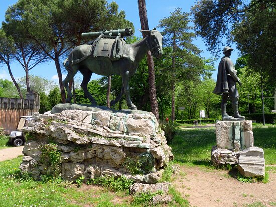 In primo piano il mulo Scudela e poco oltre la statua di un alpino
